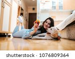 Stock photo cheerful woman playing with her dog in apartment 1076809364