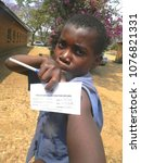 Small photo of Norton,Zimbabwe,March 3 2017,A primary school boy displaying his Measles Rubella card pointing to the spot where he was vaccinated during a vaccination program.
