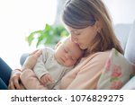 young mother  holding tenderly... | Shutterstock . vector #1076829275