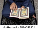 Small photo of KUALA TERENGGANU, MALAYSIA - April 15, 2017 : A man sitting on prayer mat holding an open page of Quran showing Surah Al Fatiha with finger pointing at verse or text. Quran is an Islamic Holy Book