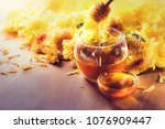 Stock photo honey in glass jar with bee flying and flowers on a wooden floor 1076909447