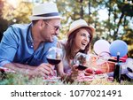 picnic time. young smiling... | Shutterstock . vector #1077021491