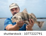 A Fisherman Is Holding A Fish ...