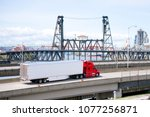 Small photo of Big rig bright red semi truck transporting semi trailer with aerodynamic skirt to reduce airflow resistance on overpass road along the river with drawbridge towers and industrial area on background