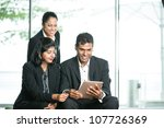 Happy Indian Business man and woman looking at a digital tablet. - stock photo