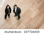 Two Indian business people looking up and smiling. - stock photo