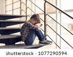 depressed little boy sitting on ... | Shutterstock . vector #1077290594