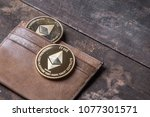 Small photo of Ethereum coin with leather wallet on old wooden table top