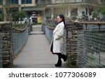 in autumn  a young woman stands ... | Shutterstock . vector #1077306089