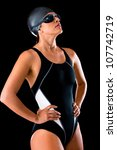 Professional female swimmer in a swimsuit wearing goggles and hat - stock photo