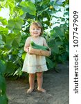 2 years child picking cucumbers in hothouse - stock photo