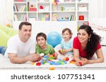 Kids with their parents playing at home - family portrait, focus on the children - stock photo