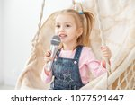 A little cheerful girl sings a song into the microphone. The concept of childhood, performer, life style, music.