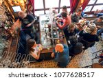 Small photo of BRUSSELS, BELGIUM - APR 2: Many people drinking beer and eating dinner in small bar with tab counter and old furniture on April 2, 2018. More than 1,200,000 people lives in Brussels