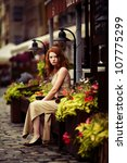 beautiful red-haired woman resting on the streets of the beautiful city - stock photo
