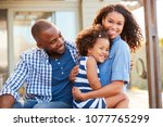 black family embracing outdoors ...   Shutterstock . vector #1077765299