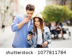 couple of tourists consulting a ... | Shutterstock . vector #1077811784