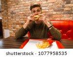 young guy eats a hamburger and... | Shutterstock . vector #1077958535