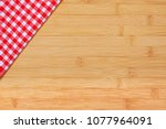 red checkered cloth on a wooden ... | Shutterstock . vector #1077964091