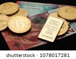 Bitcoin and credit suisse gold bar lying on swiss franc banknotes, cryptocurrency gold and cash concept
