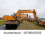 Small photo of Half a dozen excavators parked on the edge of a construction site, the weather is too bad to dig