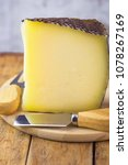 Small photo of Wedge of Spanish Artisanal Goat Cow and Ewe Cheese with Black Wax Rind on Wood cutting Board with Fork and Knife. Rustic Kitchen Interior. Mediterranean Cuisine. Poster Banner Template