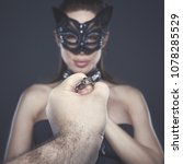 Small photo of Strong man hand holding submissive lover in mask on chain, bdsm concept