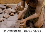 Small photo of man set on fire with fire stone for cooking in stone age