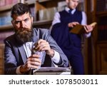 Small photo of Yellow press concept. Man in oldfashioned suit holds money. Journalist got reward for article from publisher. Writer with strict face with typewriter in library with books on background, defocused.