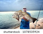 A Fisherman Is Holding A Huge...