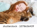 Stock photo young redhair woman sleeping with cat 1078636439