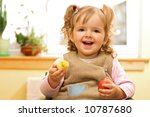 Happy girl with easter egg and decoration in hands - stock photo