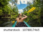 Small photo of Adventuresome Woman kayaking along a beautiful tropical jungle river. Paddling along a calm beautiful river in a scenic natural backdrop
