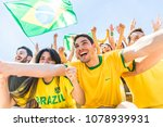Small photo of Brazilian supporters celebrating at stadium with flags. Group of fans and friends watching a match and cheering team Brazil. Sport and lifestyle concepts during international cup match
