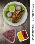 Small photo of grilled chicken fillet with vegetables (lemon, salad, onion) on a wooden background. chicken fillet grilled on a plate top view