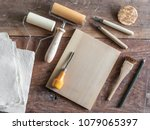 Small photo of Woodcut Art Printing Equipment for Artist, Wooden Rollers, Pencil, Chisels, Wooden Plate, Brush, Mulberry Papers on Wooden Background