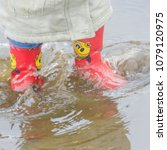 Small photo of close - up of baby in rubber boots in a puddle, wave