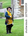 Small photo of Falmouth, Cornwall, UK - April 12 2018: Historical military re-enactor dressed in bleu and yellow Tudor clothes with leather equipment demonstrating a working musket.