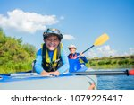 happy boy kayaking with his... | Shutterstock . vector #1079225417
