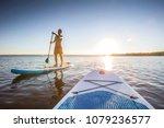 Standup paddler at the lake during sunset