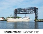 A Great Lakes freighter carrying cement passing under the Norfolk Southern Railroad drawbridge at the mouth of the Cuyahoga River in Cleveland, Ohio - stock photo