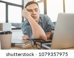 Small photo of Portrait of weary employer lying on desk with closed eyes near laptop. Exhaustion during labor concept