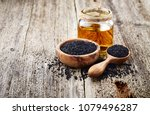 black cumin oil on wooden... | Shutterstock . vector #1079496287
