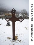 Small photo of Eresfjord, Norway- APRIL 4, 2018. Iron cross in cemetery in Sira Church or Eresfjord Church it is located in the county of Møre og rRomsdal