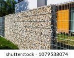 stones in a metal fence. | Shutterstock . vector #1079538074