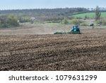farm tractor handles earth on... | Shutterstock . vector #1079631299