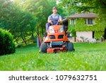 gardener driving a riding lawn... | Shutterstock . vector #1079632751