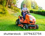 gardener driving a riding lawn... | Shutterstock . vector #1079632754