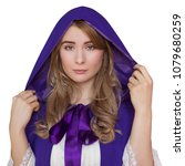 Small photo of Beautiful young woman on raincoat and hood, dressed in a white dress. Medieval costume of fantasy. A modest look, lowered eyes. White isolated background.