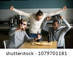 Small photo of Excited diverse men football fans celebrating victory goal score watching game online on smartphone supporting winning team drinking beer eating pizza together in pub, sport betting win concept